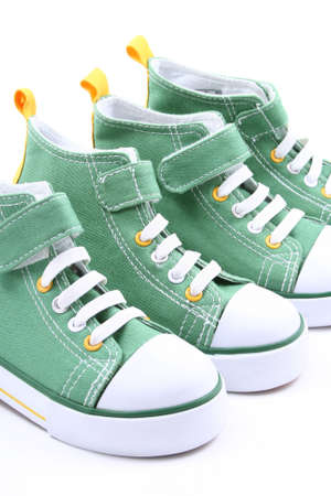 two pairs of green sneakers for children close-ups photo