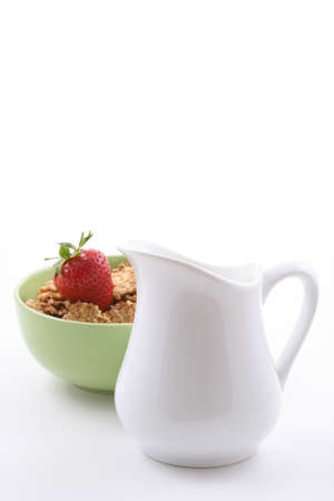 bowl of corn flakes with strawberry and jug of milk Stock Photo - 1432225