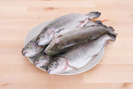 rainbow fish: plate full of rainbow trouts on table Stock Photo