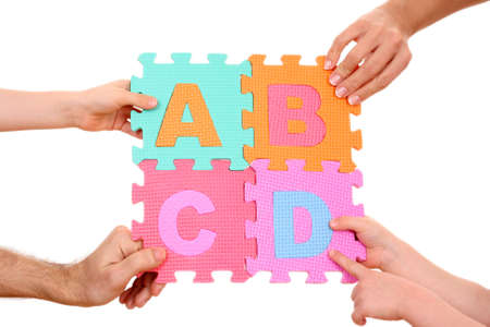 hands holding puzzle with ABCD letters isolated on white photo