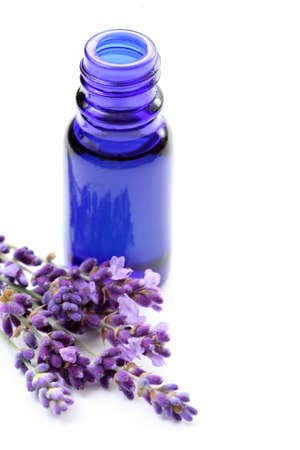bottle of lavender oil and bunch of lavender flowers Stock Photo