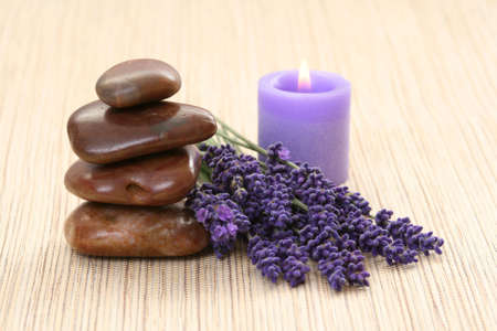 lavender flowers: bunch of lavender flowers candle and stones Stock Photo