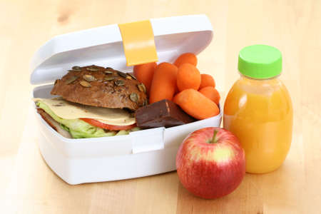 box with sandwich fruits and chocolate and bottle of juice photo