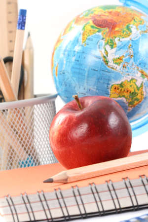 box with pencils spiral netebook and red apple on white Stock Photo - 3754740