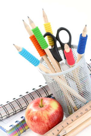 box with pencils spiral netebook and red apple on white Stock Photo - 3754748