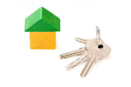 wooden house and keys isolated on white photo