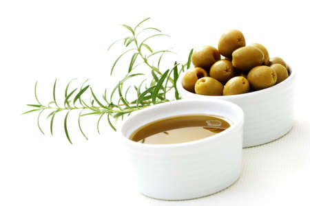 bowl of olive oil and green olives Stock Photo