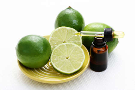 bottle of essence oil with fresh limes - beauty treatment