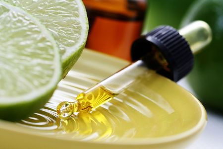 bottle of essence oil with fresh limes - beauty treatment Stock Photo - 4714067