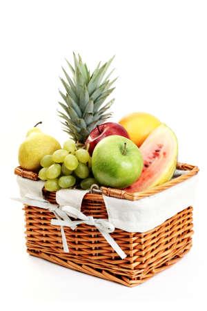 picnic basket full of delicious fruits isolated on white photo