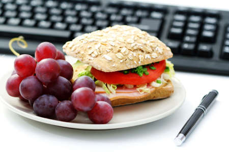 quick lunch in the office - bun and fresh grapes photo