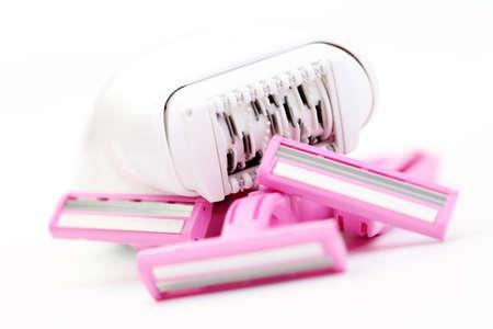pink razor and epilator on white - beauty treatment focus on epilator photo