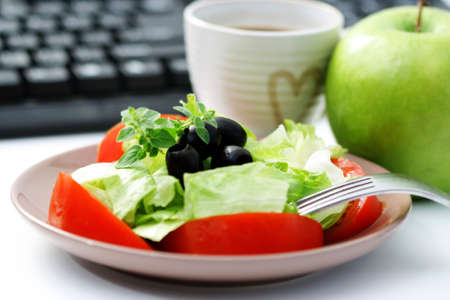 lunchtime: healthy snack in the office - plate of fresh salad