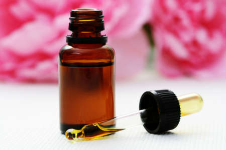 bottle of essence oil with pink flowers - beauty treatment photo