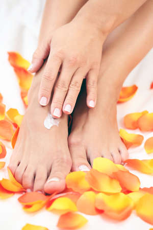 female hands and feet with petal of rose - beauty treatment photo