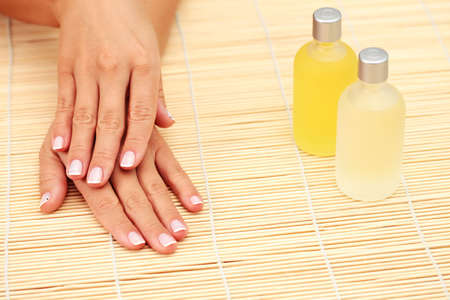 beautiful female hands and bottle of massage oil - beauty treatment photo