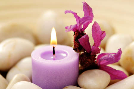lavender flowers: candle and lavender flowers in stones - relaxing time Stock Photo