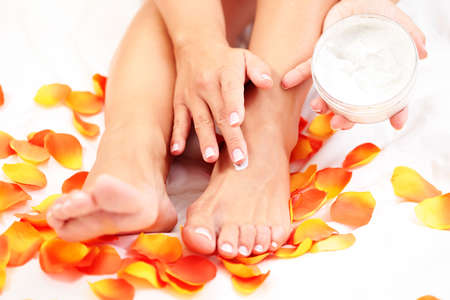 foot cream: female hands and feet with petal of rose - beauty treatment Stock Photo