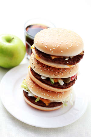 stack of hamburgers wit cola and green apple - food and drink photo