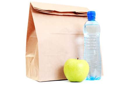 manzana agua: Bolsa de almuerzo de papel con manzana fresca y agua sobre blanco - comida y bebida