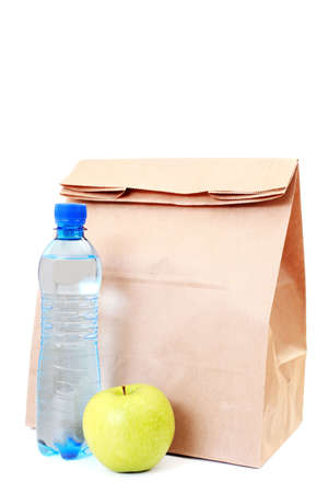 lunch break: paper lunch bag with fresh apple and water on white - food and drink Stock Photo