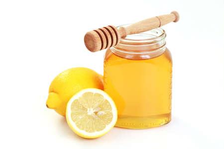 cold remedy: honey and lemon on white - alternative medicine Stock Photo