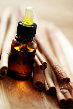 stick of cinnamon: bottle of cinnamon essential oil - beauty treatment
