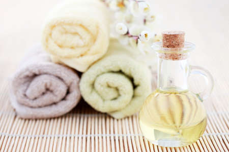 massage oil: bottle of massage oil with towels and flower - beauty treatment