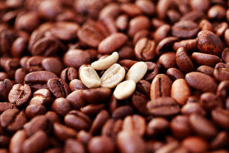 unroasted: background of roasted and few unroasted coffee beans - coffee time Stock Photo