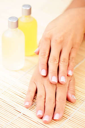 massage oil: beautiful female hands and bottle of massage oil - beauty treatment