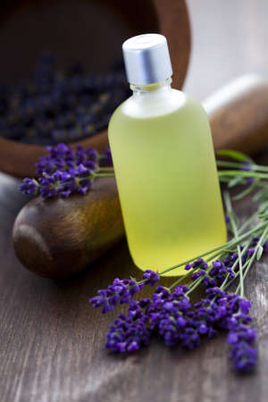 massage oil: bottle of lavender massage oil with mortar and pestle - beauty treatment