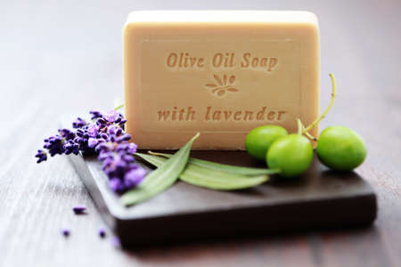 grooming product: bar of herbal soap with fresh herbs and olives - beauty treatment Stock Photo