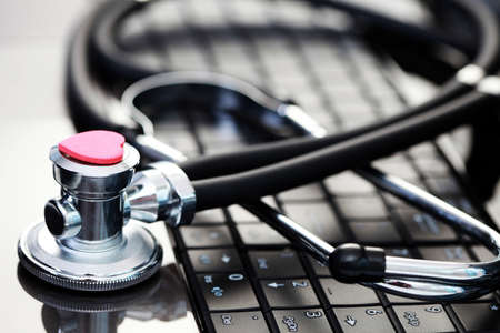 close-ups of laptop and stethoscope as a medical help photo