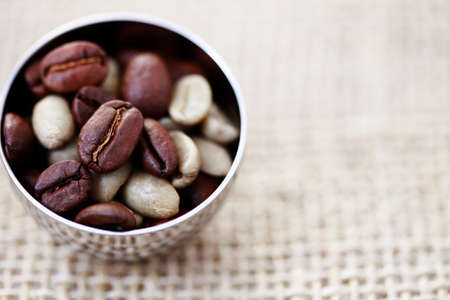 unroasted: spoon of roasted and unroasted coffee beans - coffee time Stock Photo