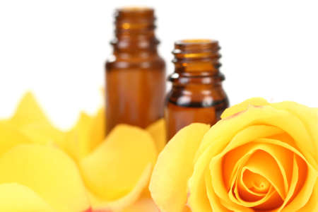 bottles of essential oil and beautiful rose isolated focus on rose photo