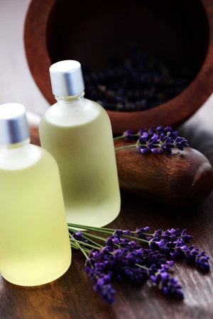 bottle of lavender massage oil with mortar and pestle - beauty treatment