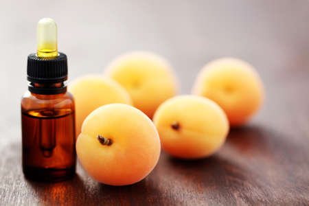 bottle of essential oil with fresh apricots - beauty treatment photo