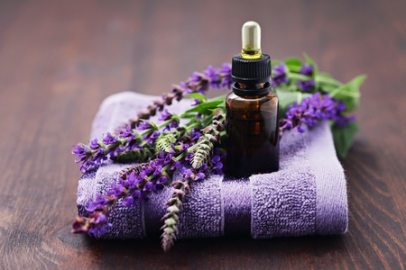 sage essential oil with fresh sage and towel - beauty treatment