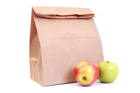 lunch break: paper lunch bag with fresh apples on white - food and drink focus on fruits Stock Photo