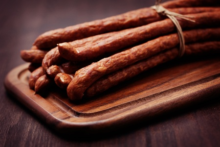 dried sausages on wooden cutting board - food and drink