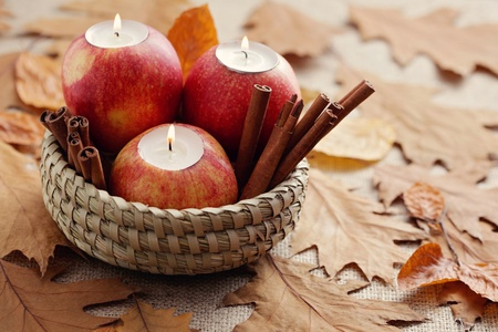 red apple as candlestick with cinnamon and autumn leaves