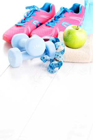fitness concept with dumbbells and green apple - sport and leisure