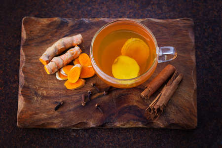 aromatic turmeric tea with cinnamon cloves and ginger - healthy eating Stock Photo