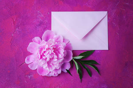 pink envelope with beautiful peony flower - love is in the air