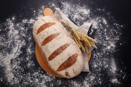 loaf of bread with ears of wheat on black background - food and drink