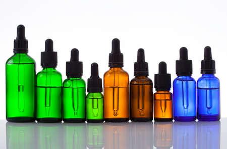 Botellas de cosméticos con pipeta sobre fondo blanco. Foto de archivo