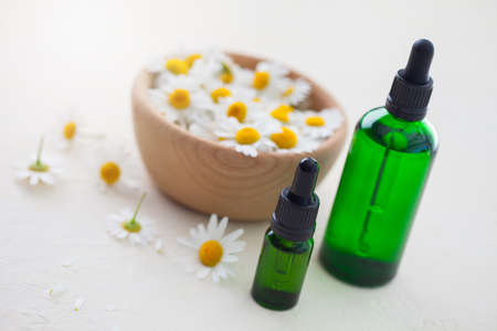 aromatherapy essential oil with camomile flowers - beauty treatment