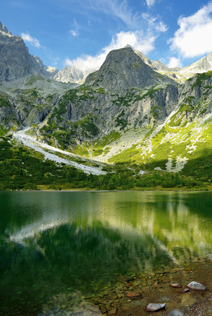 tarn: High Tatras in Slovakia. Green lake and monumental peaks. Summer landscape scenic mountain view.