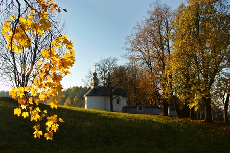 Calvary in Slovakia. Christian church in Banska Bystrica. Falling leafs in autumn landscape, Catholic chapel with a cross symbol.