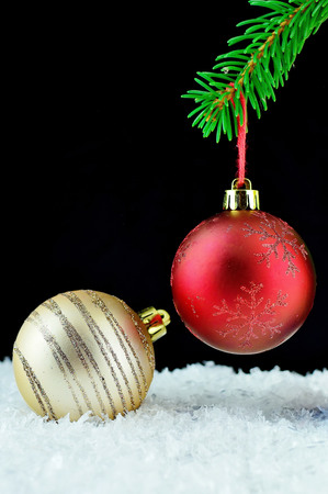 bough: Red christmas ball on green bough. Beautiful christmas close-up decoration with black background. Gold christmas ball on white snow.